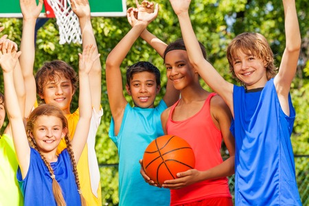niños en recreo: Amigos sostienen los brazos hacia arriba en el baloncesto juego de pie al aire libre durante el día soleado de verano