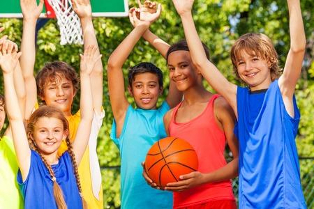 Vrienden houden armen omhoog in basketbal spel staan buiten tijdens zonnige zomerdag