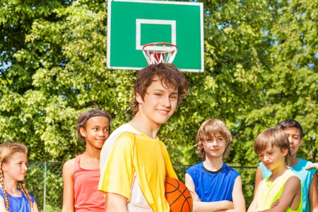 international basketball: Smiling boy with international friends standing behind at basketball game outside during sunny summer day