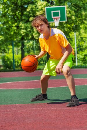 Boy playing with ball alone during basketball game outside during sunny summer day