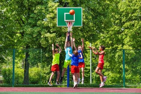 Gelukkige tieners spelen basketbal op een speelplaats in de zomer