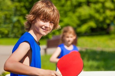 tischtennis: Jungen und Mädchen spielen zusammen draußen im Sommer sonnigen Tag Lizenzfreie Bilder