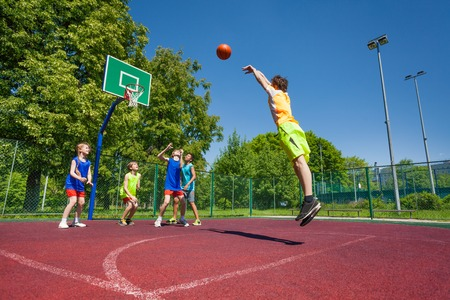 Boy performs foul shot at basketball game on the playground during sunny summer day