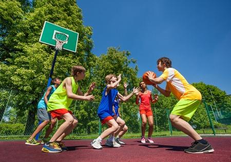 Los adolescentes que juegan al juego de baloncesto juntos en el patio durante el día soleado de verano Foto de archivo