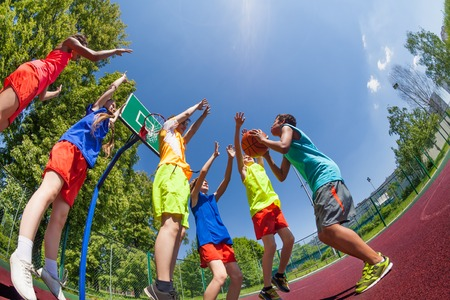 basketball: Fisheye view from below of teenagers playing basketball game together on the playground during sunny summer day