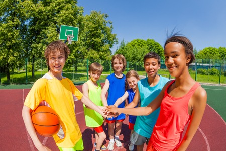 Close-up of teens before basketball game hold arms in star shape at playground outside during sunny summer day