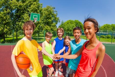 Close-up van tieners voor basketbal spel houden armen in ster vorm op speelplaats buiten tijdens zonnige zomerdag