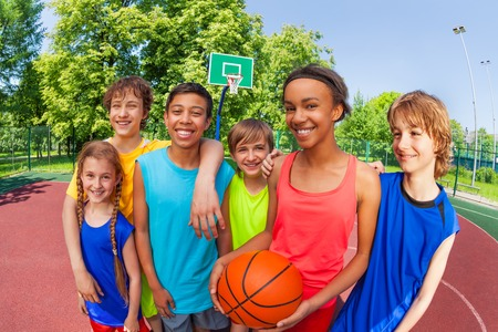 Basketball teenage team standing close after game outside during sunny summer day close-up view