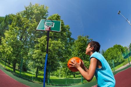 playground basketball: Arabian boy ready to throw ball in basketball goal on the playground outside during sunny summer day Stock Photo