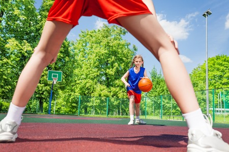 children sport: Girl with ball view between two legs of opposite player during basketball game on the playground outside