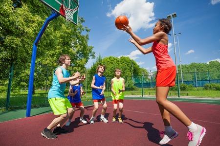 화창한 여름 날 함께 10 대들이 땅에서 농구 경기를 함께하고있다.
