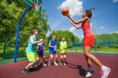 Teenagers are playing basketball game on the ground during sunny summer day together Reklamní fotografie