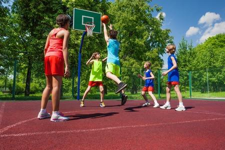 niños en recreo: Equipo con uniformes coloridos que juegan al juego de baloncesto en el suelo durante el día soleado de verano juntos Foto de archivo
