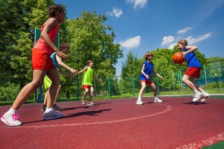 ティーンエイ ジャーが一緒に日当たりの良い夏の日の間に遊び場で遊ぶバスケット ボールの試合をチームします。