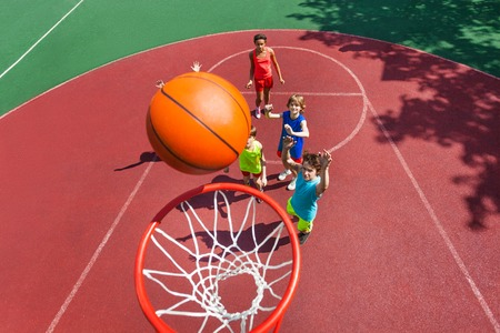 basket: View of flying ball to the basket from top during basketball game with kids standing on the ground down