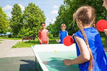 Four international friends playing table tennis  outside during summer sunny day Stock Photo