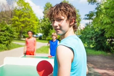 kids outside: Boy with racket turned and playing table tennis with friends outside during summer sunny day Stock Photo