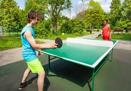 pingpong: Niña africana y niño jugando al aire libre durante día soleado de verano