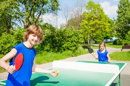 Boy with racket serves table tennis ball to girl outside during summer sunny day