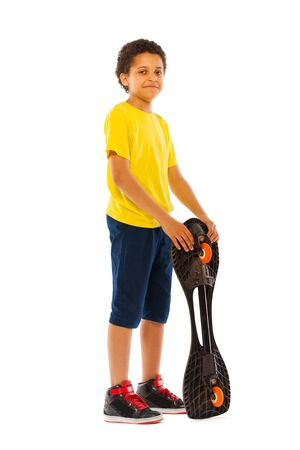 full height: Nice little African black boy standing with skate board in full height isolated on white side view