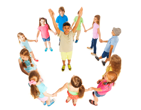 hands lifted up: Cute school age boy with lifted up hands standing in the circle of diverse looking kids Stock Photo