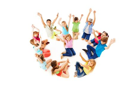 lift hands: Large circle of kids sit together with one girl in the middle all lift hands Stock Photo