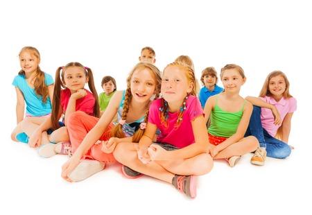 amistad: Lindo retrato de grupo de niños con dos mejores amigos sentados y sonrientes en la primera fila aislados en blanco