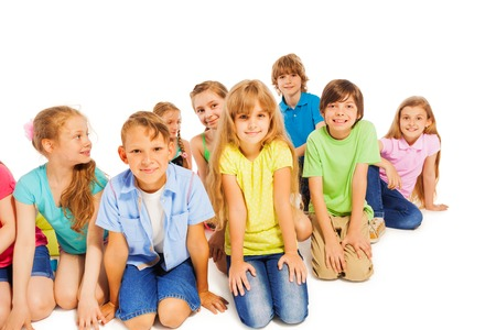 young boys: Group of 8 years old kids hanging out sitting isolated on white Stock Photo
