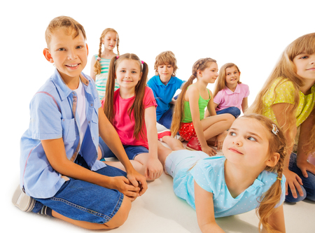 year old: Funny 8 year old kids hang out, sitting laying down, relaxing isolated on white