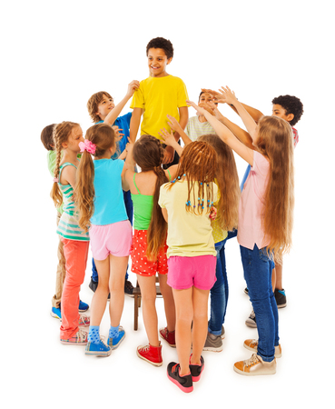 popularly: Full length group portrait of boys and girls circle black boy and stretch hand toward him
