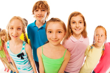 wide angle lens: Group of happy kids, boys and girls together stand and look up smiling to wide angle lens with focus on a girl Stock Photo