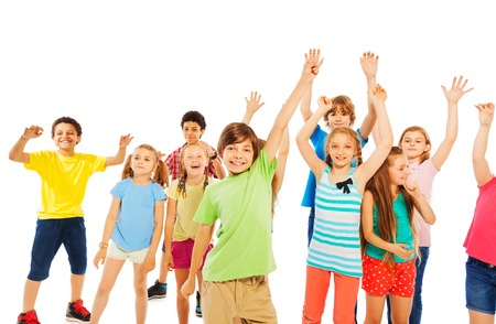 Group of happy kids rising hands and cheering standing in a group together isolated on white