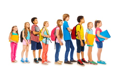 to queue: Happy children standing in a line holding textbooks isolated on white side view Stock Photo