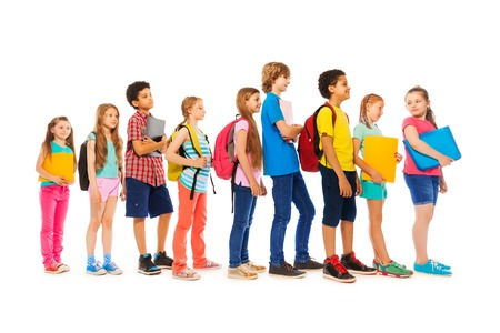 to queue: Group of kids boys and girls in a line side view Stock Photo