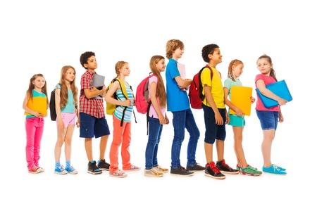 niño con mochila: Grupo de chicos y chicas niños en una vista lateral de línea Foto de archivo