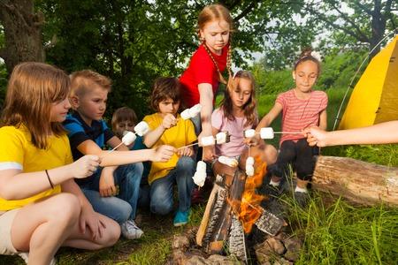 Kinder sitzen in der Nähe von Lagerfeuer mit Marshmallow während Camping im Wald zusammen