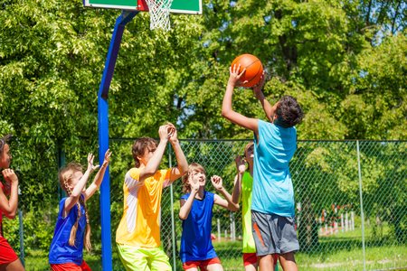 Groep tieners het spelen van basketbal op speelplaats in de zomer