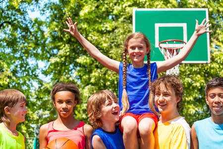 international basketball: Girl with arms up sits on shoulders of international friends after basketball game outside during sunny summer day