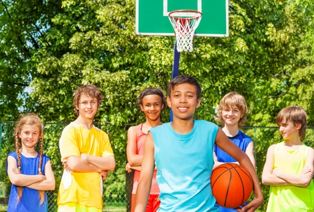 international basketball: Arabian boy with international friends standing behind at basketball game outside during sunny summer day