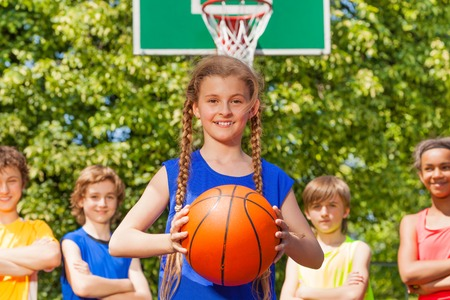 team from behind: Girl with ball and her team standing behind at basketball game outside during sunny summer day