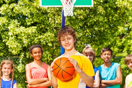 international basketball: Boy with ball and international friends standing behind at basketball game outside during sunny summer day