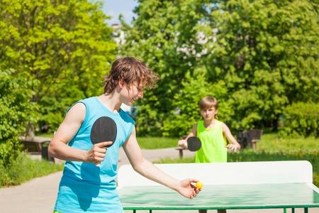 ping pong: Dos ni�os jugando juntos ping pong al aire libre durante d�a soleado de verano Foto de archivo