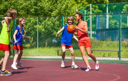 child sport: African girl holds ball and teenagers playing basketball on playground during summer