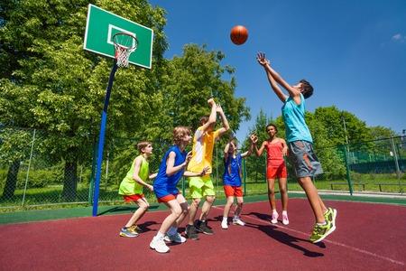 canestro basket: Adolescenti che giocano gioco a basket insieme al parco giochi durante soleggiata giornata estiva