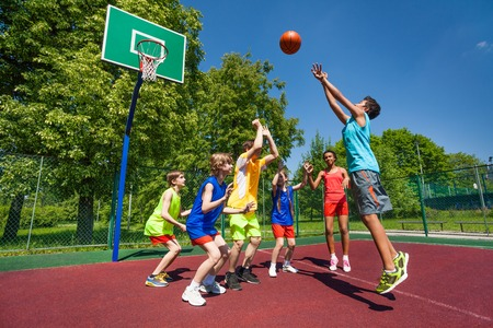 Teenagers playing basketball game together on the playground during sunny summer day