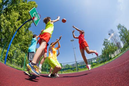 De mening van Fisheye van de tieners het spelen van basketbal spel samen op de speelplaats tijdens zonnige zomerdag Stockfoto