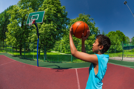 boy ball: Arabian boy throwing ball in basketball goal on the playground outside during sunny summer day