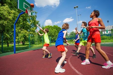 balones deportivos: Los adolescentes con uniformes coloridos que juegan al juego de baloncesto en el suelo durante el día soleado de verano juntos