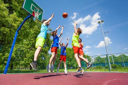 baloncesto: Los ni�os saltan para la bola volar durante el juego de baloncesto en el suelo en el d�a soleado de verano juntos