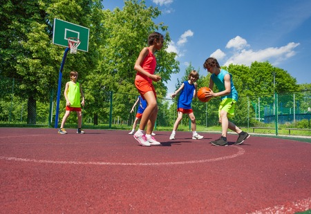 kids jumping: Boys and girl playing basketball game on the playground during sunny summer day together